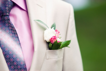 buttonhole: the grooms buttonhole from a rose outdoors