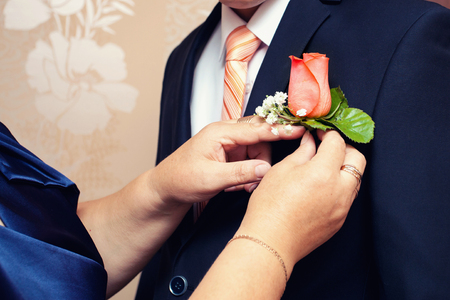 hands of mother correct a buttonhole for the groom