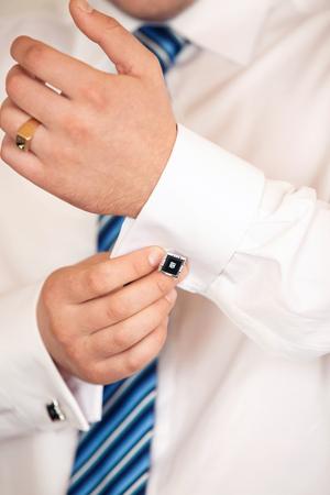 cuff: The man clasps a cuff link on a shirt