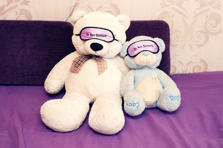 teddy bears on a violet sofa with a bandage in the eyes