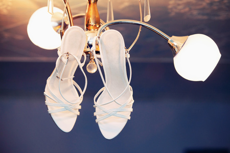 stilleto: wedding shoes of the bride on a chandelier Stock Photo