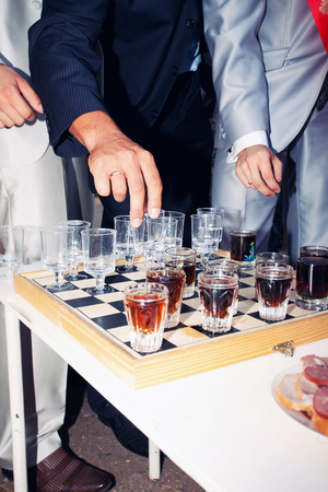 drunks: Wineglasses as chess figures on a glass chessboard