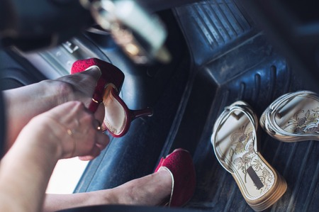 A woman's foot with high heels pressing the brake pedal of a car