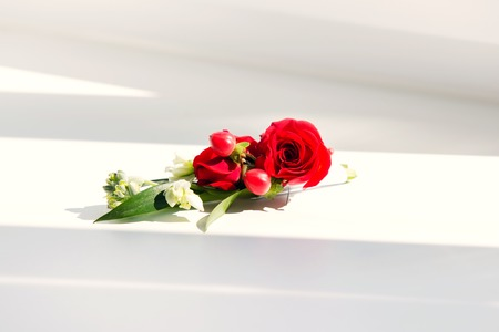 the grooms buttonhole from a red rose and red berries