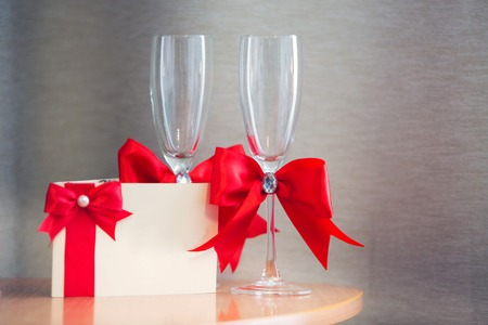 affiance: invitation on a wedding and glasses for the newlywed with a red tape Stock Photo