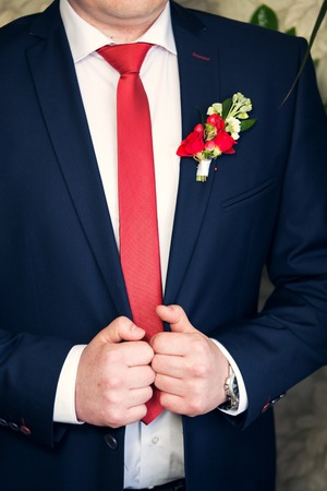 buttonhole: the grooms buttonhole from a red rose and red berries