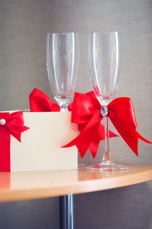invitation on a wedding and glasses for the newlywed with a red tape Stock Photo