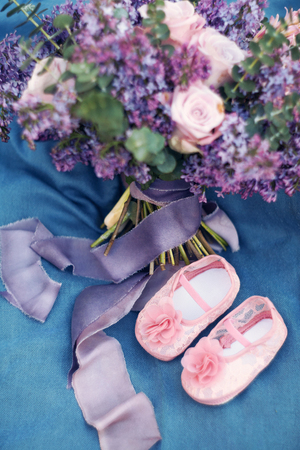 beautiful spring bouquet from a lilac and roses on blue fabric Foto de archivo