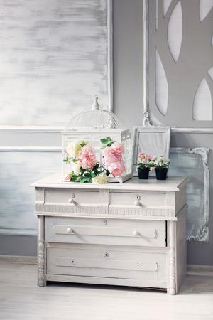 antique vase: Flowers on antique commode. Flowers (Hydrangea) in a tin vase on an antique commode. Stock Photo