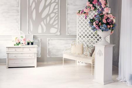 큰 창문과 봄 꽃이있는 고전적인 실내 공간에 흰색 가죽 빈티지 스타일 가구