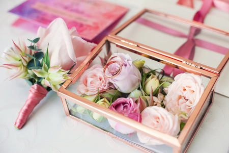 Glass box for a wedding rings decorated with fresh flowers and the grooms buttonhole from a rose