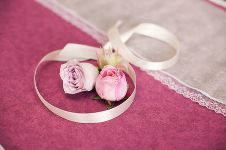 claret: buds of a rose and beige tape on a claret background. Wedding attributes