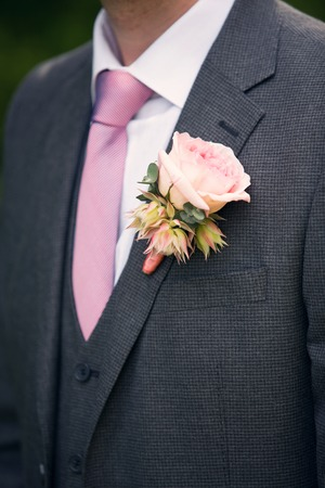 wedding rose boutonniere in grooms tuxedo with rose tie Stock Photo