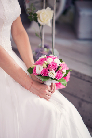 bouquet from roses in the brides hands. Pink tapes Stock Photo
