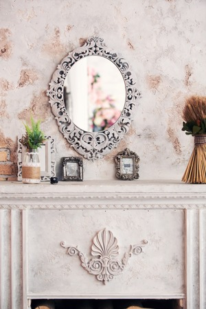 victorian fireplace: fireplace in classical style and a mirror in an interior Stock Photo