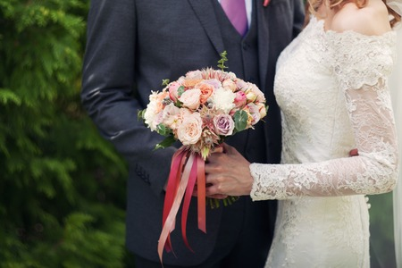 arm bouquet: bouquet from roses in the brides hands. Pink tapes Stock Photo