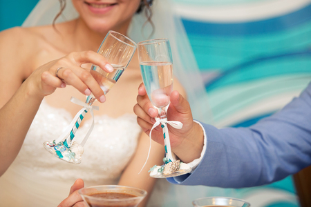 glasses of the groom and bride in hands with a blue tape