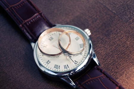 mans watch: A mans and womans wedding rings . A mans wrist watch is in the background out of focus.