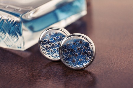 cuff link: Silver Cufflinks with blue insert on wodden background Stock Photo