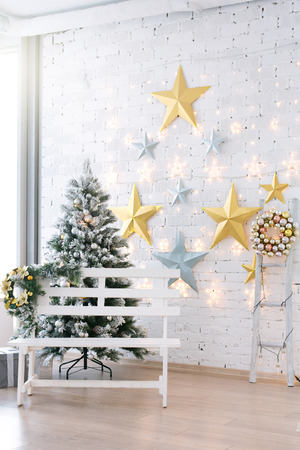 Decorated Christmas tree in classical interior design of white hall.