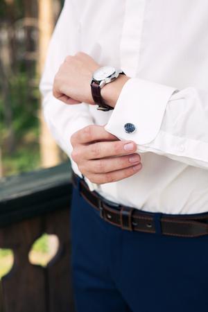 cuffs: man buttons cuff-link on cuffs sleeves luxury white shirt
