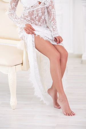 morning of the bride. beautiful harmonous legs of the girl. The bride in a peignoir Stock Photo