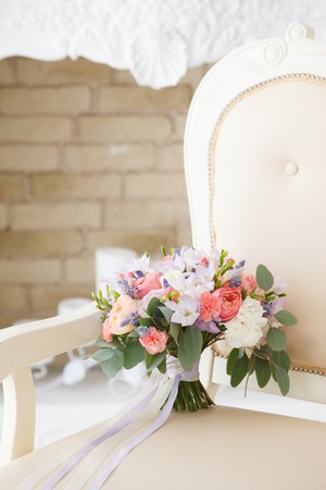gentle bridal bouquet from pink peonies and white roses on a vintage sofa in a classical interior Stock Photo