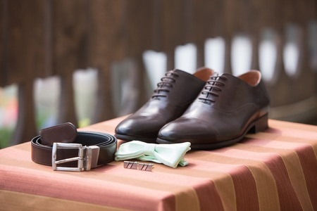 accessories of mens wear. Brown shoes and leather belt, bow-tie of green color and cuff link. Morning of the groom, wedding concept