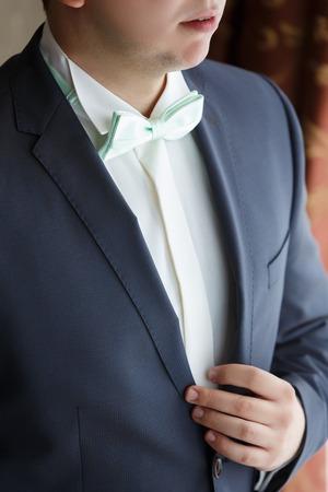 El hombre en un esmoquin negro y una corbata verde. Mañana del novio, concepto de la boda Foto de archivo
