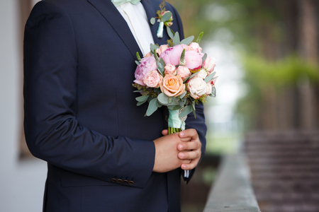 groom waiting for the bride holds in hand a bouquet from pink peonies. Wedding day