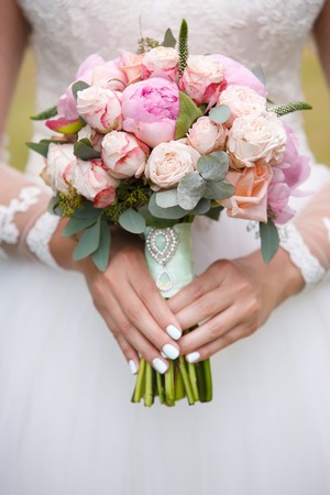bride holds in hand the bouquet from pink peonies outdoors. Wedding day