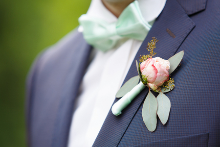 wedding rose boutonniere in grooms tuxedo with rose