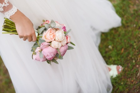 bride holds in hand the bouquet from pink peonies outdoors on a green lawn. Wedding day