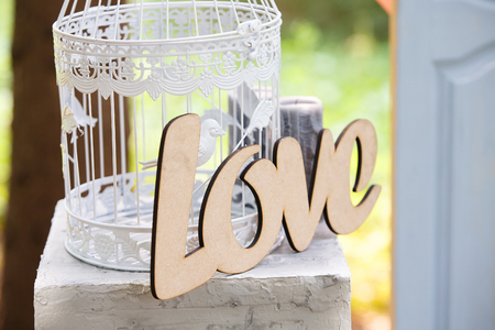 decor in the form of a birds cage and a wooden inscription with the word love