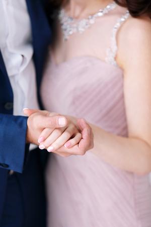 Novia y el novio que llevan a cabo las manos juntas