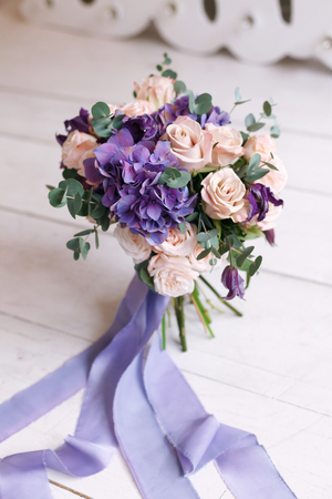 Ramo de novia de rosas rosas y una hortensia violeta y cintas de seda en una mesa de madera Foto de archivo
