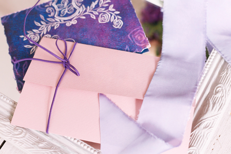 invitation on a wedding of pink color and violet tapes. Wedding concept