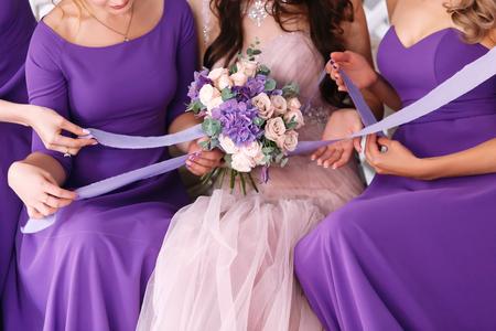 Fila de damas de honor y novia en vestidos de violeta con ramos de flores en la ceremonia de la boda Foto de archivo