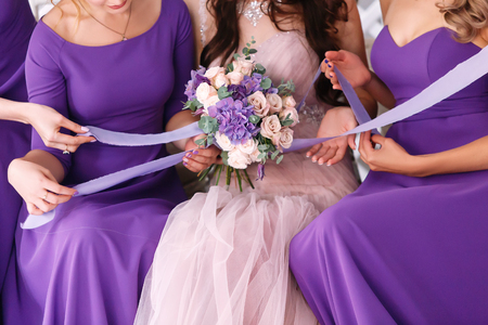 Row of bridesmaids and bride in violet dresses with bouquets at wedding ceremony