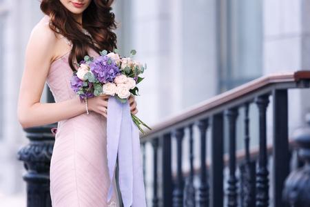 La novia tiene un ramo de boda de color violeta y rosa