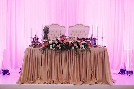 Mesa de boda para el recién casado en color violeta decorado con flores
