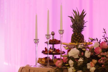 La mesa de vacaciones está decorada con velas, flores y frutas. Violeta Foto de archivo