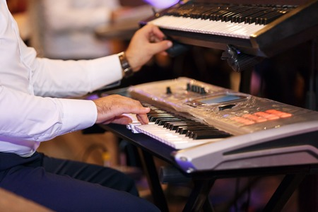 the musician plays a synthesizer