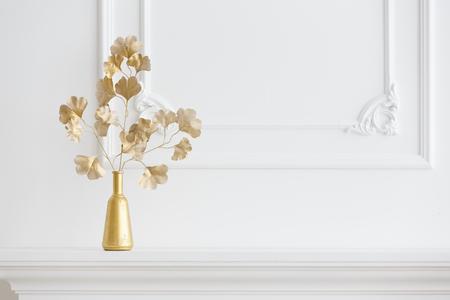 Interior blanco. Chimenea blanca en un interior ligero y un jarrón de oro. Interior clásico