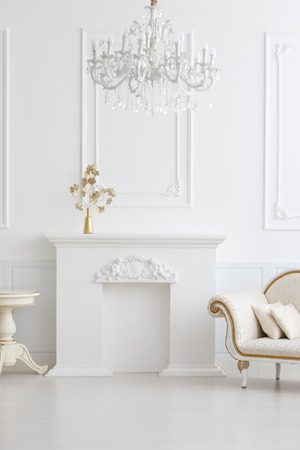 beautiful classical white interior with a fireplace, a sofa and a vintage chandelier. Retro, classics