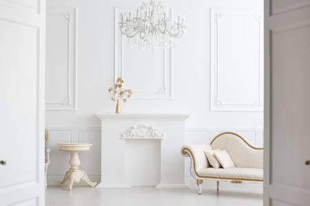 hermoso interior blanca clásica con una chimenea, un sofá y una lámpara de araña de la vendimia. Retro, clásicos