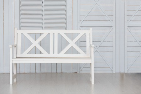 Vintage white Bench Against blue wooden Wall Foto de archivo