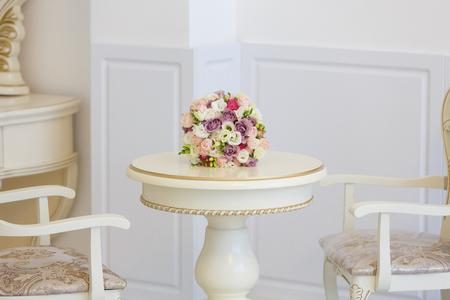 Ramo de flores sobre una mesa en un interior ligero. Estilo barroco, muebles blancos caros Foto de archivo