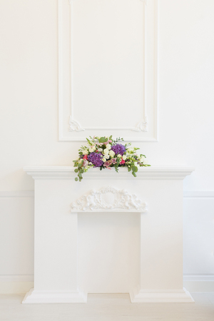 Elegant white fireplace full of flowers instead of fire. Elegant room Foto de archivo