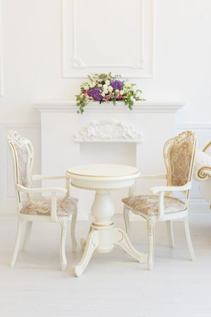 White table and chair in a living room. Modern classics with rococo elements
